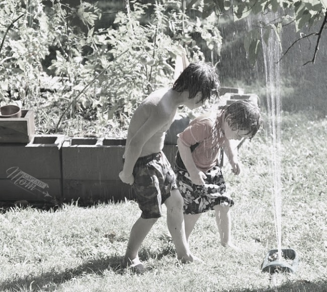 two boys playing in backyard sprinkler